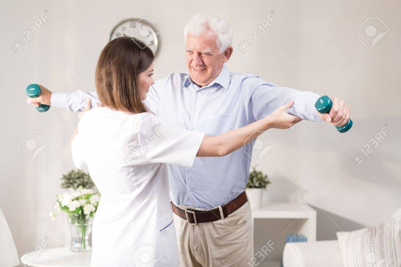 49486134 nurse helping patient to exercise with dumbbells